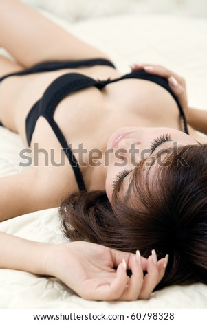 Sexy woman in black lingerie lying on the bed,upside down,a hand touching her breast - stock photo