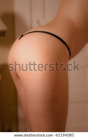 Sexy woman in black thong in her bedroom - stock photo