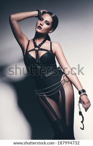 sexy woman in black with opened handcuffs - stock photo
