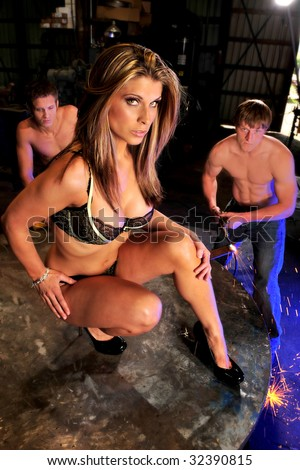 sexy woman in bra and panties kneeling on table in welding shop with men with cutting torch in background