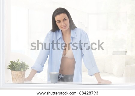 Sexy woman in bra and shirt standing at window with coffee mug, smiling.?