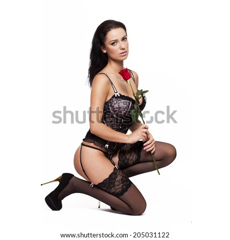 Sexy woman in corset and stockings squat smell rose, isolated on white background - stock photo