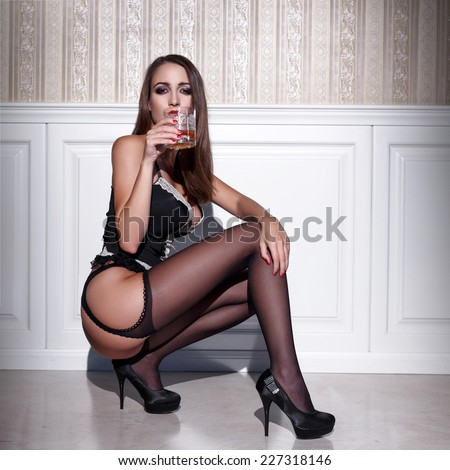 Sexy woman in corset and stockings squat with whiskey, seduction - stock photo