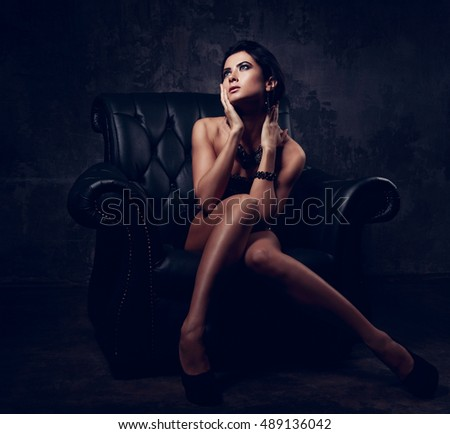 Sexy woman in fashion dress posing in luxury black armchair and looking up. Dark dramatic shadow light