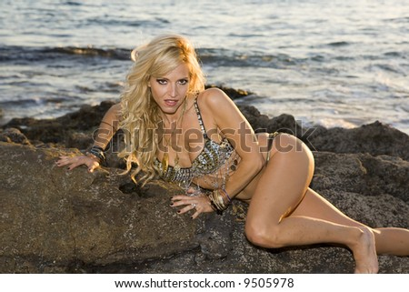 Sexy Woman in flashy outfit on rocks at the Beach. - stock photo