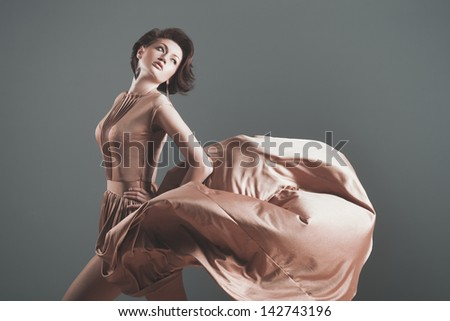 Sexy woman in fluttering gold dress - stock photo