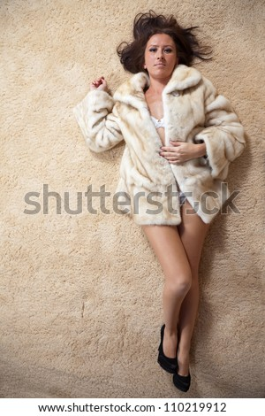 Sexy woman in fur coat over  carpet - stock photo