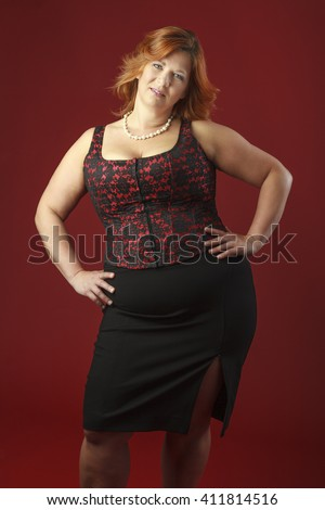 sexy woman in her forties wearing a red corset - stock photo