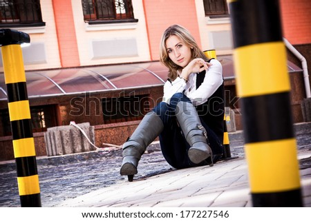Sexy woman in high boots sitting on parking  - stock photo
