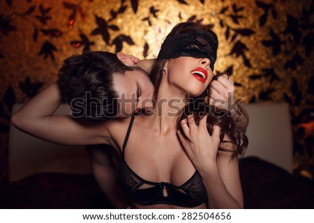 Sexy woman in lace eye cover and red lips with young lover, foreplay in hotel room - stock photo