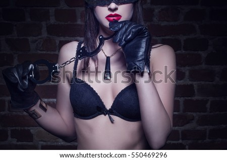Sexy woman in lace eye cover holding handcuffs closeup