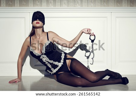 Sexy woman in lace eye cover with handcuffs, posing on floor at vintage wall - stock photo