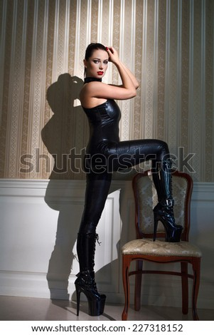 Sexy woman in latex catsuit step on chair at night - stock photo