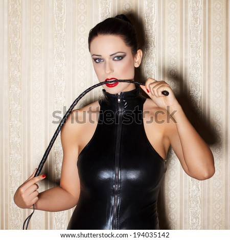 Sexy woman in latex catsuit with whip in mouth, desire - stock photo