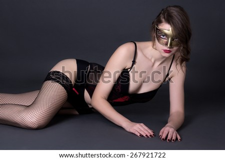 sexy woman in lingerie and mask lying over grey background - stock photo