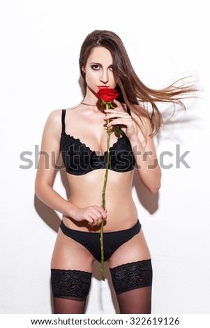 Sexy woman in lingerie and stockings smell rose at white wall, on white background - stock photo
