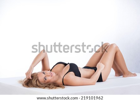 Sexy woman in lingerie lying on her back - stock photo