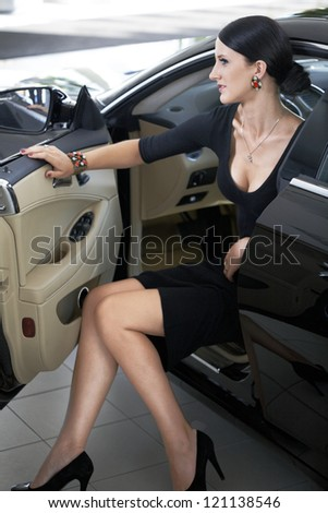 Sexy woman in luxury car with long legs - stock photo