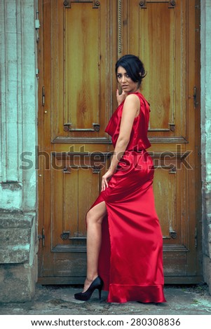 Sexy woman in red dress in front of door. Outside fashion shooting. Red dress. Beautiful girl in sensual red dress. - stock photo