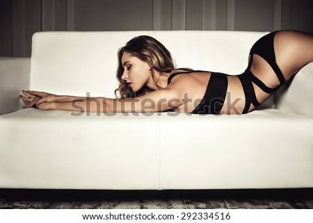 sexy woman in seductive black lingerie lying on a couch - stock photo