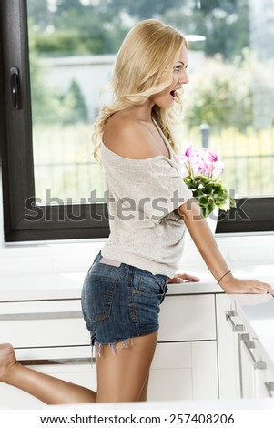 sexy woman in short looking with surprise outside from the window home , she is standing on one legs - stock photo