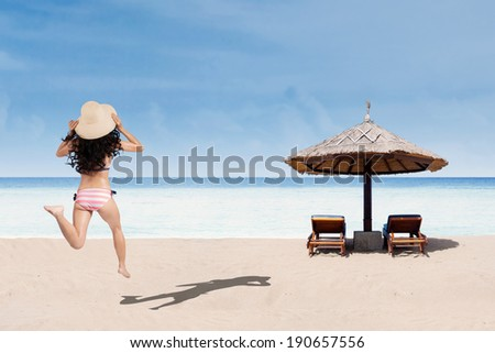 Sexy woman in striped bikini running at beach. shoot at summertime - stock photo