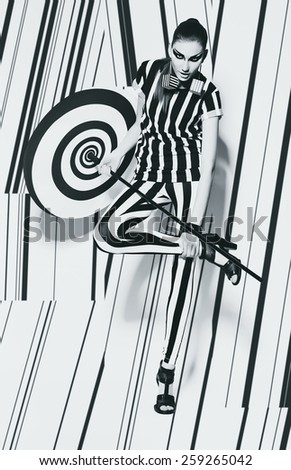 sexy woman in striped top and leggings with umbrella in studio - stock photo