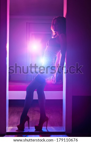 Sexy woman in underwear standing at the door of bedroom. Toned image with low light effect. - stock photo