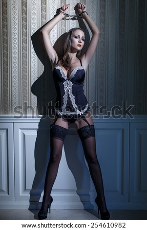 Sexy woman in underwear with handcuffs posing at night, bdsm - stock photo