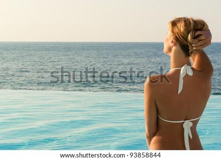 Sexy woman in white bikini near edge of infinity pool looking far on horizon. Crete. Greece - stock photo