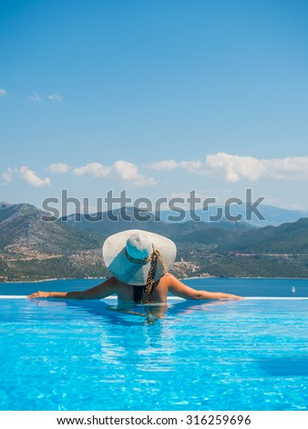 Sexy woman in white bikini relax at the infinity pool in Greece - stock photo