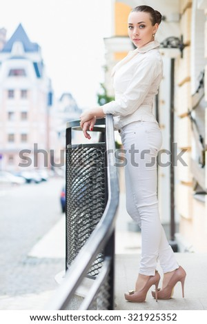 Sexy woman in white pants and jacket posing outdoors - stock photo
