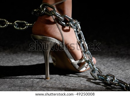 Sexy woman legs in high heel shoes in chains - stock photo