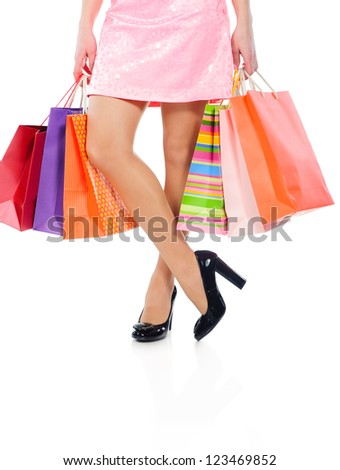 Sexy woman legs with colorful shopping bags isolated on white