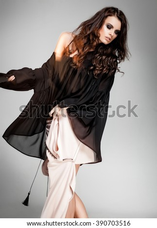 sexy woman model with curled hair dressed in fluid silk clothes posing dynamic