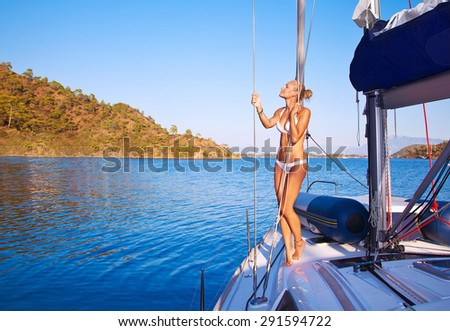 Sexy woman on sailboat, pretty girl with perfect body tanning on the deck of water transport, active beach holidays, enjoying summer vacation - stock photo