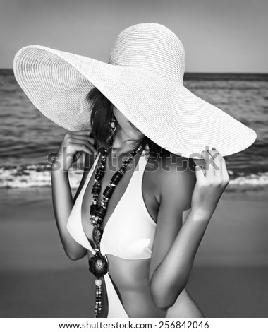 Sexy woman on the beach, black and white photo of fashion model posing on seashore, wearing a big hat, and covers her face, fashionable summer photo shoot - stock photo