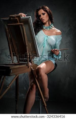 Sexy woman painting, studio shot - stock photo
