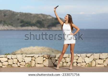 Sexy woman photographing a selfie with a smart phone on the beach in summer vacations - stock photo