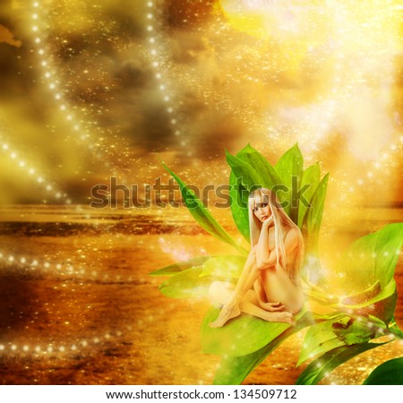 Sexy woman pixie with flower on hand  sitting on green grass in golden fantasy magic world - stock photo