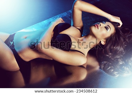 sexy woman posing in black sensual lingerie with blue light coming from behind. Fashion shot
