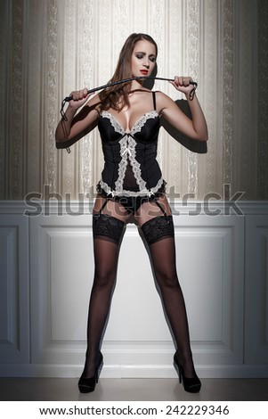 Sexy woman posing with whip at vintage wall - stock photo