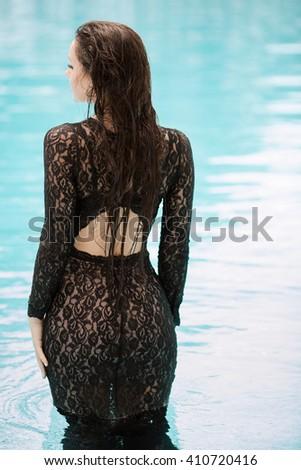 Sexy woman relaxing in black fashion dress in pool. Creative photosessin of beautiful caucasian girl.  - stock photo