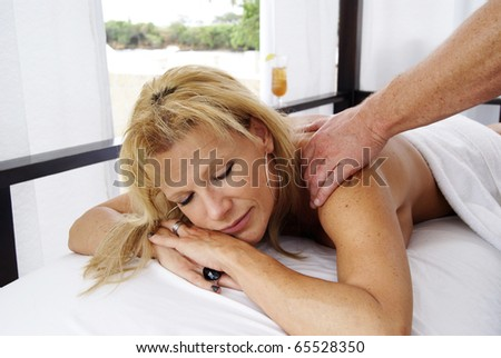 Sexy woman relaxing massage at the beach - stock photo