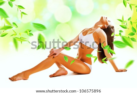 Sexy woman siting on the floor with leaves - stock photo