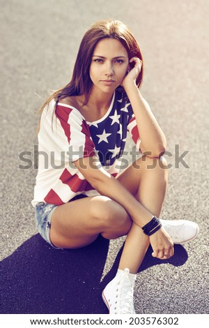 Sexy woman sitting on the ground at the sunset  - stock photo