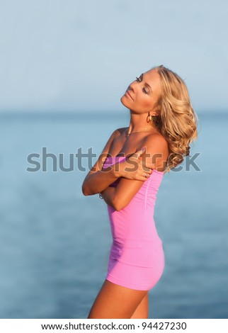 sexy woman standing at beach enjoying the view of sea - stock photo