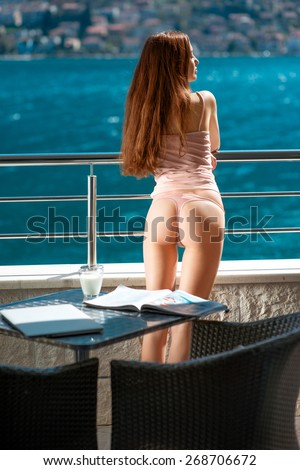 Sexy woman standing on the balcony and enjoying beautifull view on the sea - stock photo