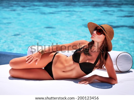 Sexy woman tanning on the beach, lying down on white luxury sofa, spending summer holidays on Maldives resort - stock photo