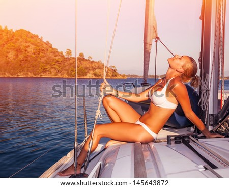 Sexy woman tanning on yacht, enjoying warm sunlight, seductive model wearing white stylish swimwear and posing on deck of sailboat in sunset light, summer holidays - stock photo